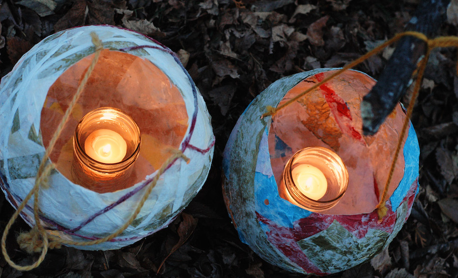 Two paper lanterns with lit candles inside them.
