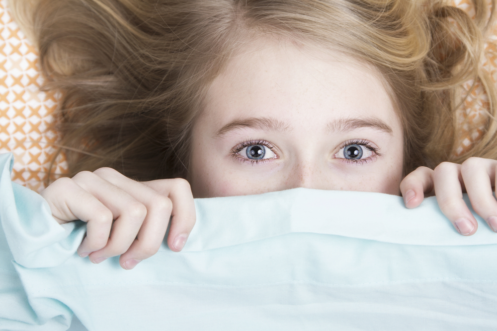 Young child hiding face under a blanket