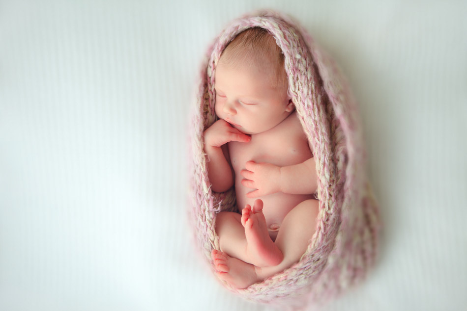 infant wrapped in pink blanket