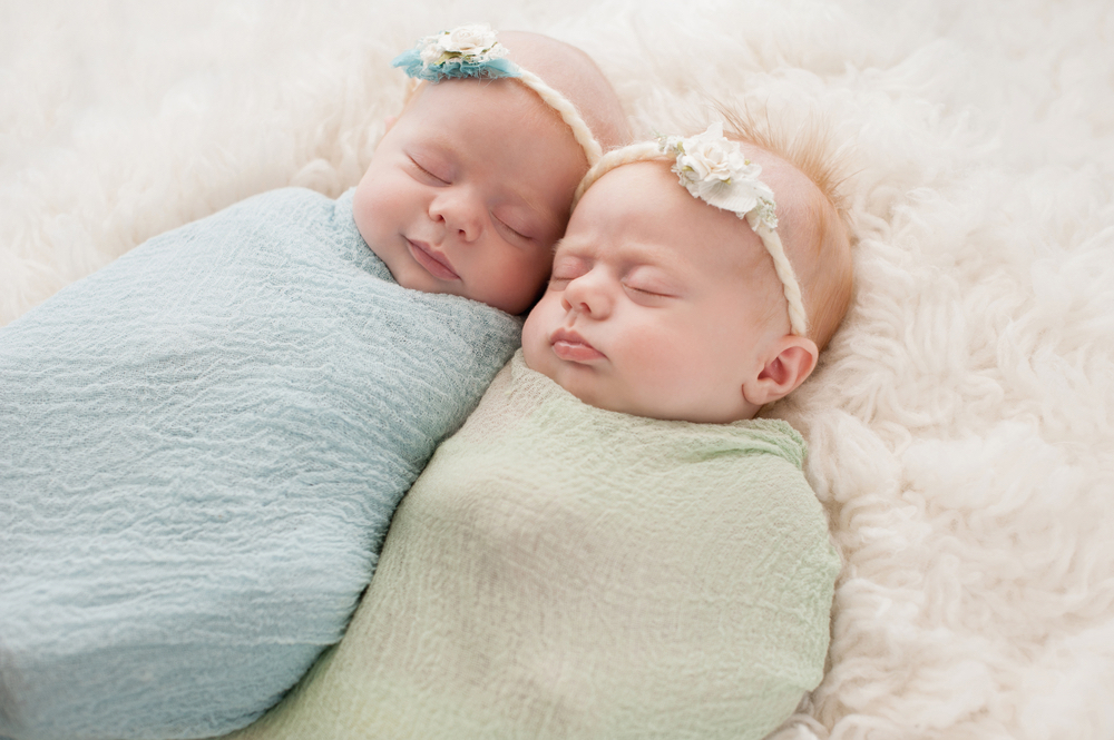 Two twin babies swaddled, sleeping side by side