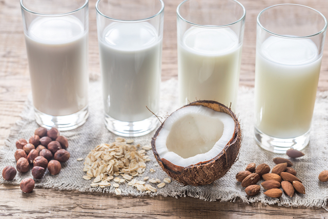 A line of alternative non-dairy milk sources in tall glasses