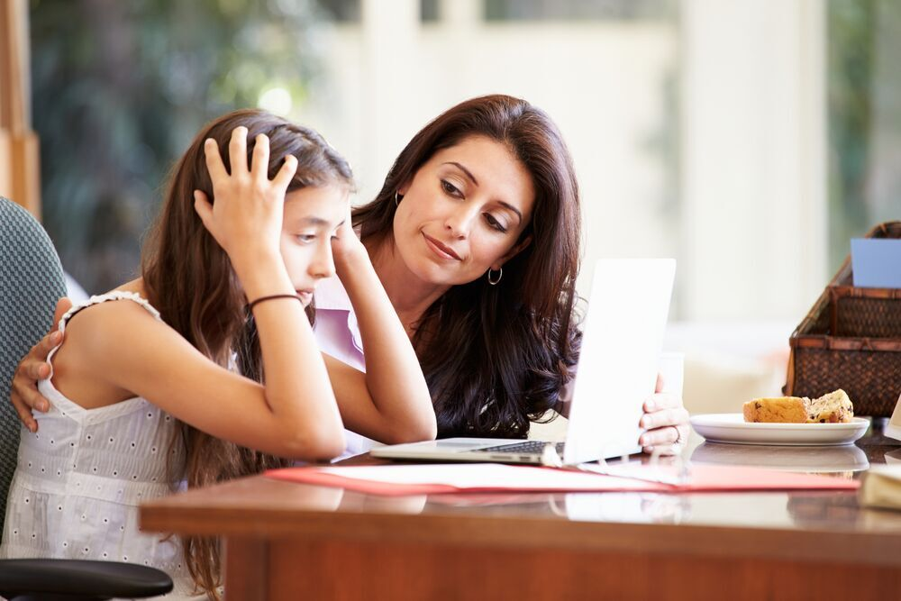 Young girl stressed over school work with mother