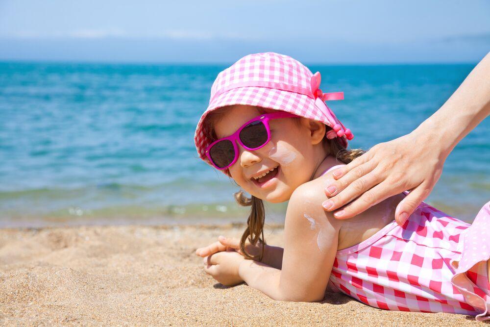Sunscreen on a little girl lying on the beach