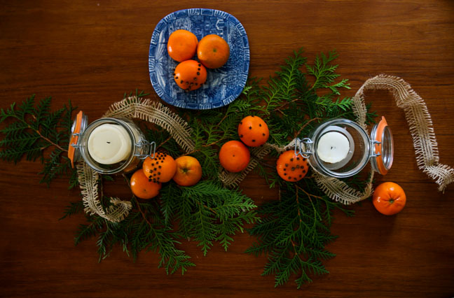 tablescape of pomander, candles, evergreen