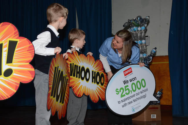 Rhonda Brothers, divisional sales manager at Staples Corner Brook, and Immaculate Heart of Mary students, Joey Lyver, left, and Thomas Randell celebrate after announcing to the school that they won $25,000 worth of new technology from Staples Canada. (The Canadian Press Images)