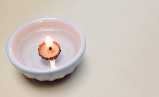 Acorn cap candle floating in a bowl of water
