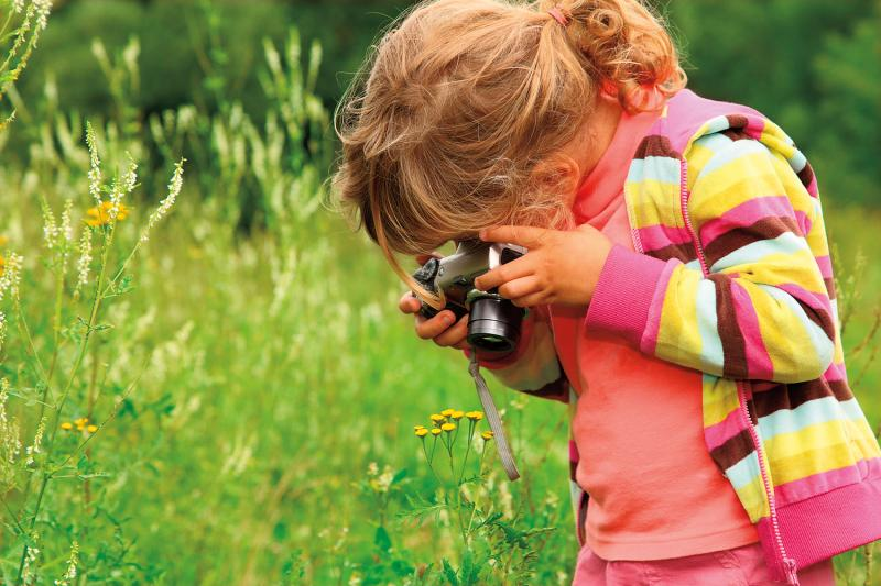young girl taking picture with camera pointed towards the ground