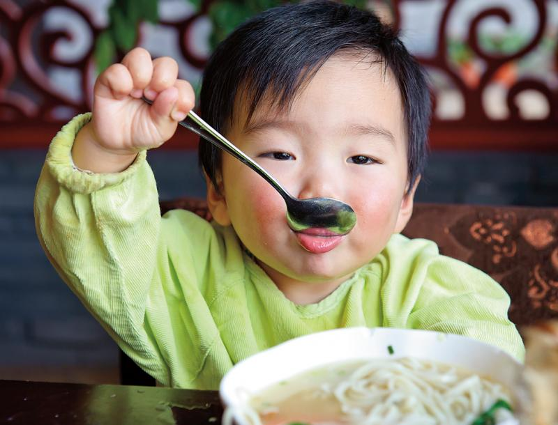 toddler eating noodle soup