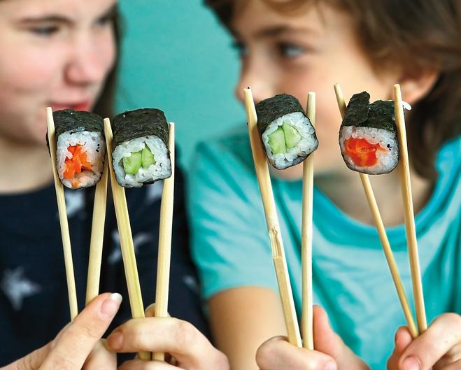 two young teens holding sushi rolls between chopsticks