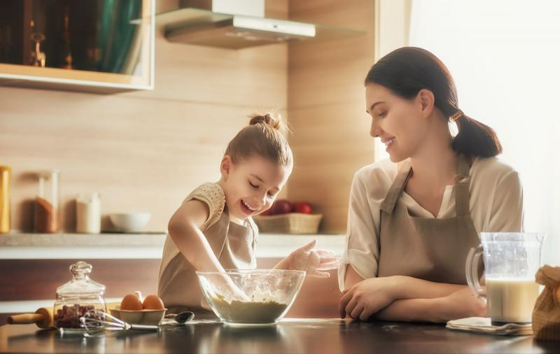 woman and young girl making food at the kitchen counter