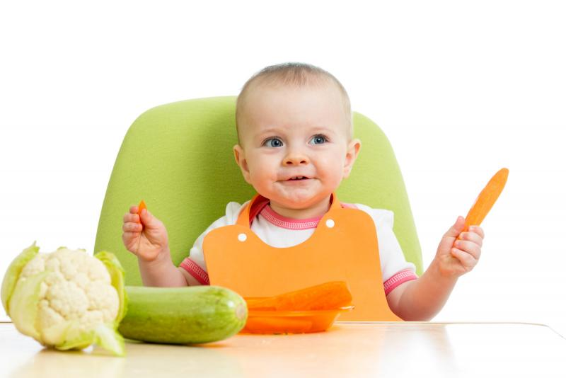 baby in green highchair with raw vegetables on table