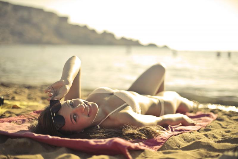 woman lying on beach looking back at camera with sunglasses pulled up