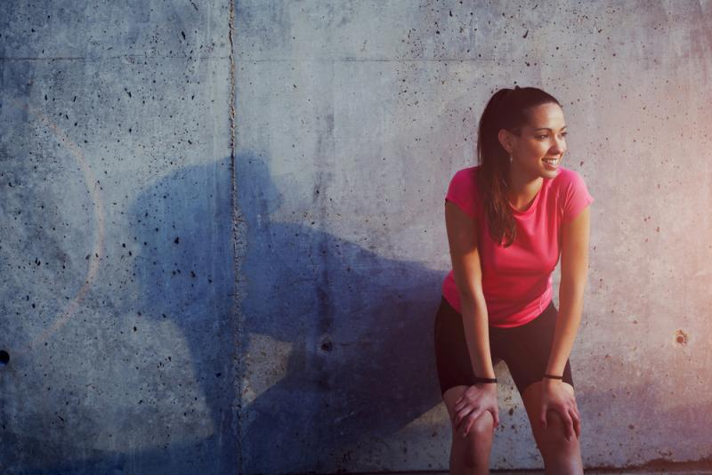 athletic woman resting against a wall