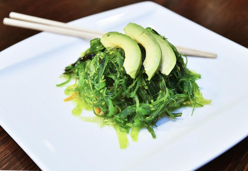 seaweed on a plate garnished with avocado