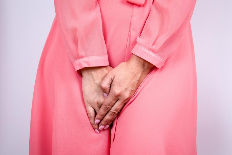 Woman wearing a pink silk dress squeezing her legs together because she has to urinate