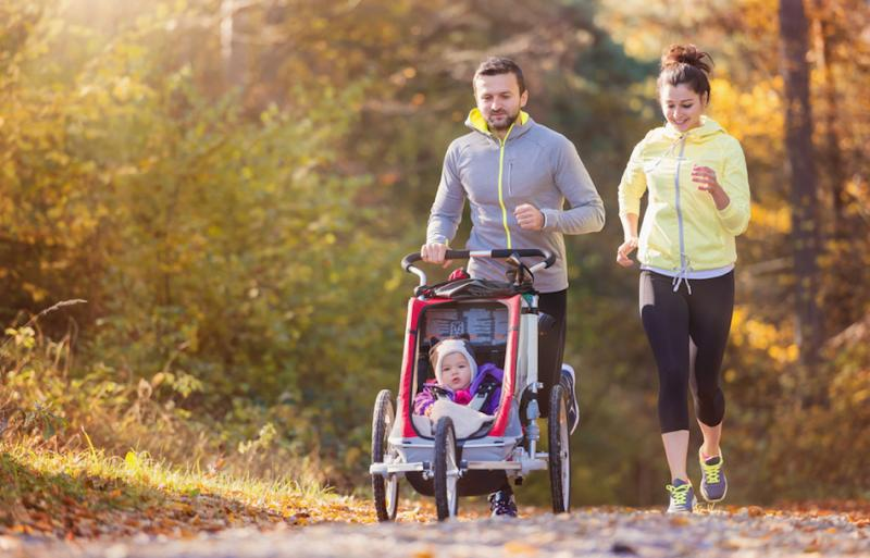 man and woman jogging with baby in stroller