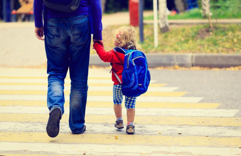 parent holding hands with small child wearing backpack viewed from behind