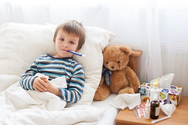 sick boy in bed with thermometer and teddy bear