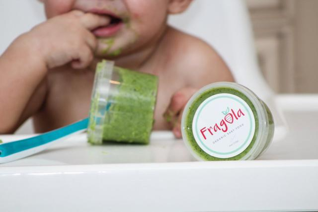 green baby food with baby tasting behind it