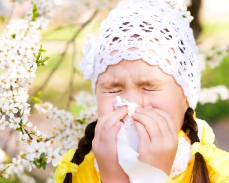 little girl in crocheted hat sneezing