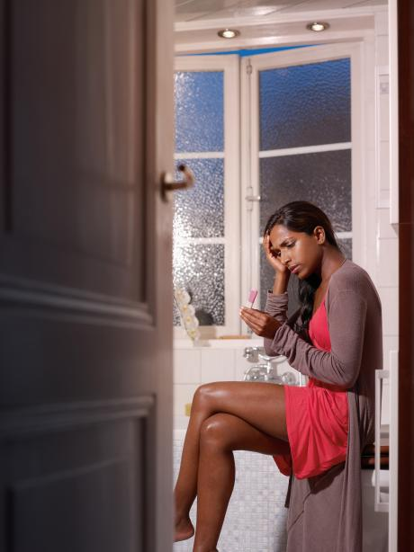 woman sitting in bathroom looking at pregnancy test