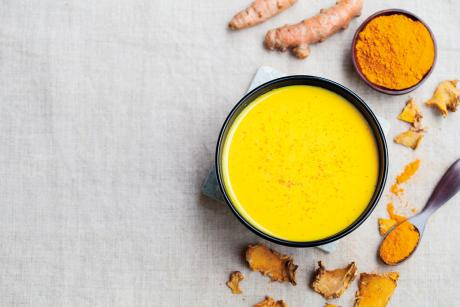 mug of turmeric latte, fresh turmeric and ground turmeric seen from above on a white tablecloth
