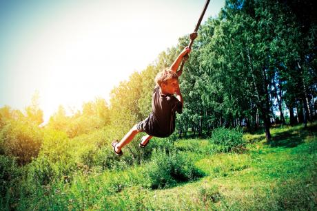 boy swinging on rope swing looking behind him
