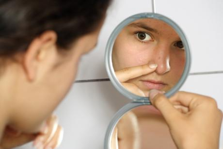 woman closely checking her face in a mirror