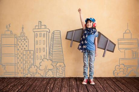 child dressed up with airplane wings against a wall with buildings drawn on it