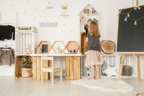 little girl in neatly organized playroom