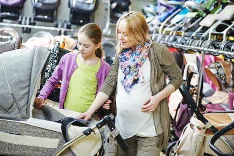 pregnant woman in a store selecting a stroller