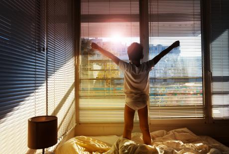 young child waking up and stretching while standing on the bed and looking out the window