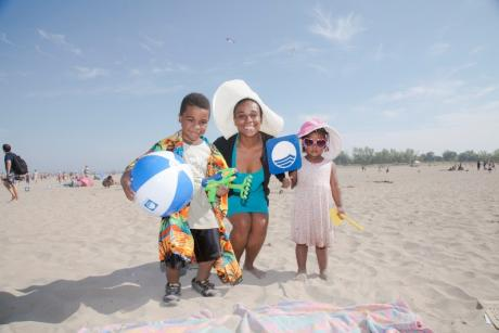 mom and two kids pose on the beach with a Blue Flag poster