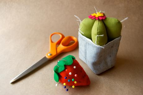 a hand-sewn cactus craft with scissors and a strawberry pin cushion nearby