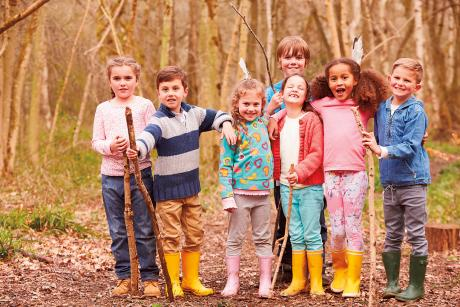 seven children wearing rubber boots playing in the woods