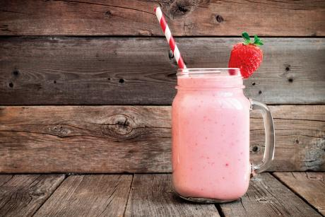 strawberry smoothie in a Mason jar with red striped straw against wooden background