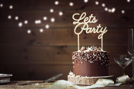"chocolate cake with a candle that says ""let's party"""