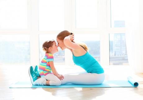mom doing sit-ups while her child sits on her legs