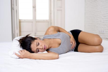 woman suffering with cramps on her bed