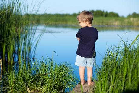 small boy stands beside a pond