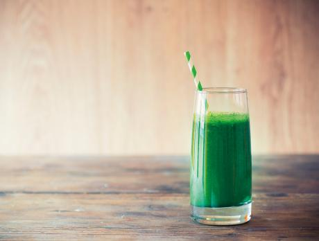 green smoothie with a green striped straw
