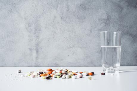 assortment of vitamins and supplements on a table next to a glass of water
