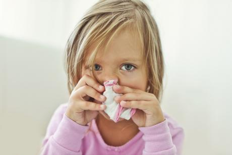 small girl holding a handkerchief over her nose