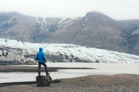 view of a person from behind looking at the snowy mountainous natural environment