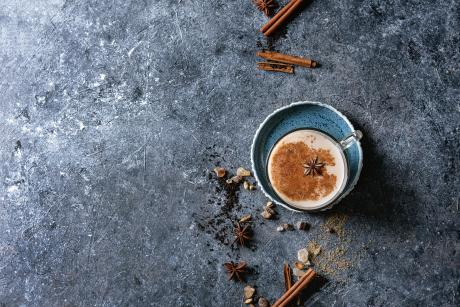 Cinnamon, cardamom, anise, sugar, black tea over dark texture background
