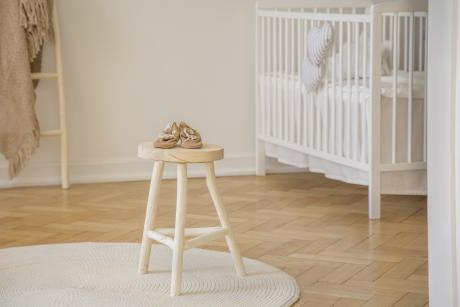 baby shoes placed on wooden stool standing in white kid room interior with crib, round rug