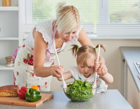 mom helping toddler toss salad