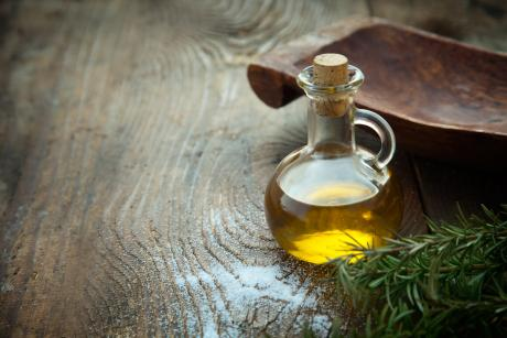 bottle of olive oil on wooden background