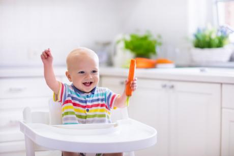 A 9 or 10 month old baby sits in a high chair holding a carrot