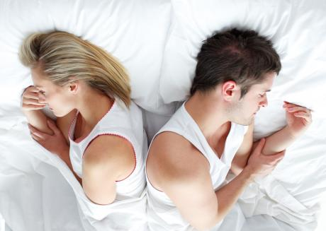 A couple face away from each other in bed